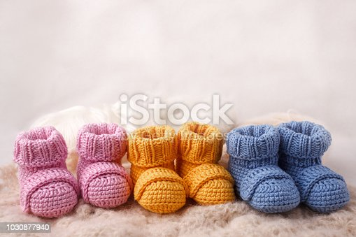 pregnancy concept, Three pairs of baby booties on a light background
