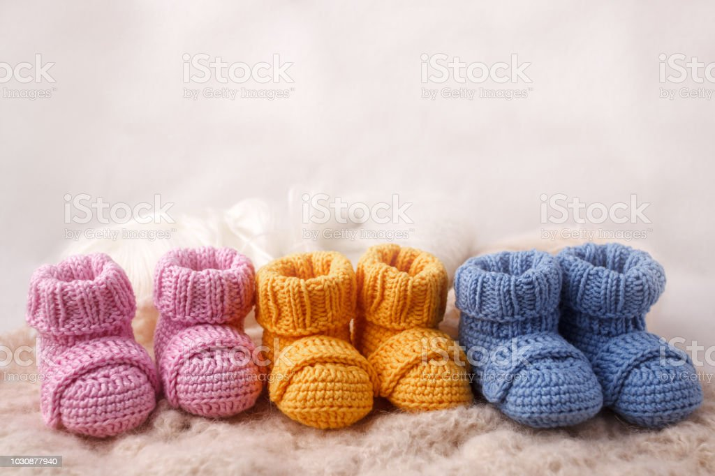 pregnancy concept, Three pairs of baby booties on a light background stock photo