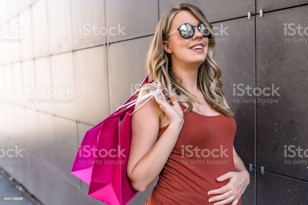 pregnancy, motherhood, people and expectation concept - happy smiling pregnant woman with shopping bags at city street. Young woman with shopping bags walking out from shop stock photo