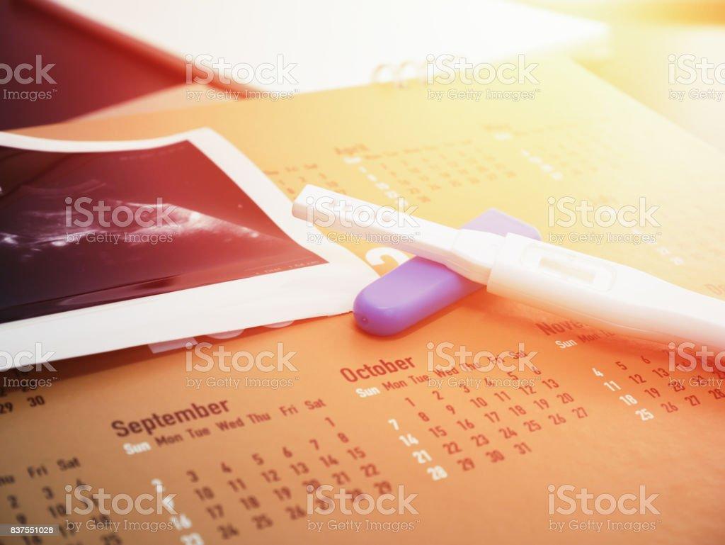 prueba de embarazo en calendario con fondo de ultrasonido - foto de stock
