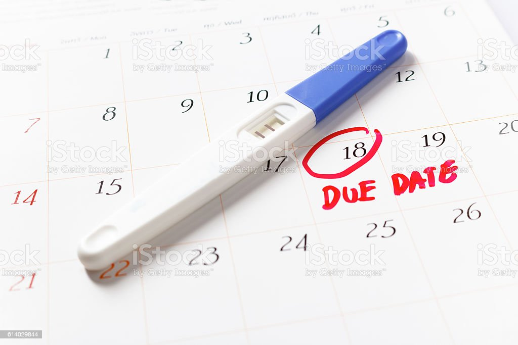 Pregnancy test with positive result lying on calendar, Due Date Pregnancy test with positive result lying on calendar; Due Date day; the 18th; Red circled on a white calendar; soft focus. Activity Stock Photo