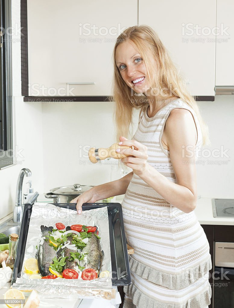 pregnancy woman cooking trout fish royalty-free stock photo