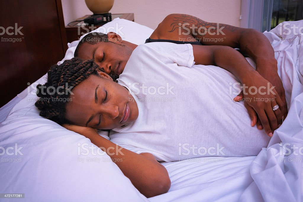 Pregnant African American black couple spooning in bed royalty-free stock photo