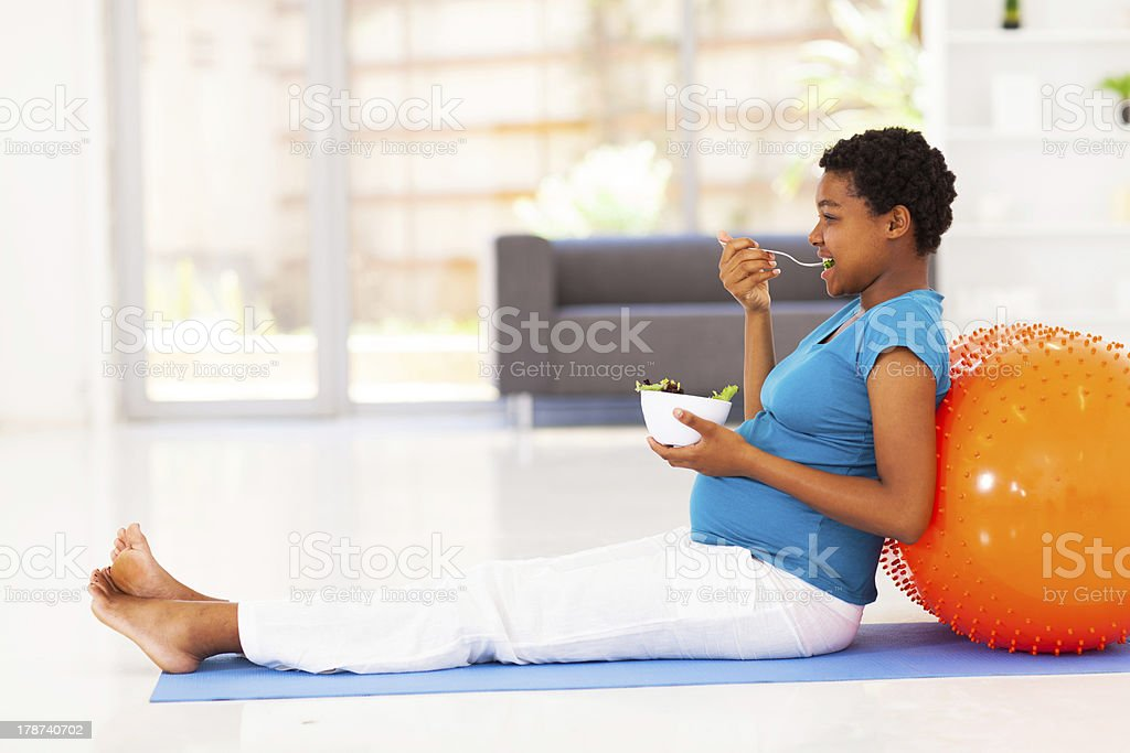 pregnant african american woman eating healthy salad on exercise mat stock photo