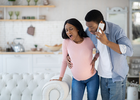 Pregnant African American woman having prenatal contractions, worried husband calling doctor on smartphone. Black lady giving birth to baby, her partner arranging medical help