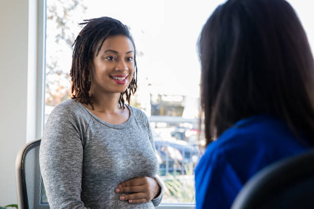 Pregnant African American woman meeting with doctor Pregnant African American woman meeting with a doctor.  Doctor is a female wearing scrubs. midwife stock pictures, royalty-free photos & images