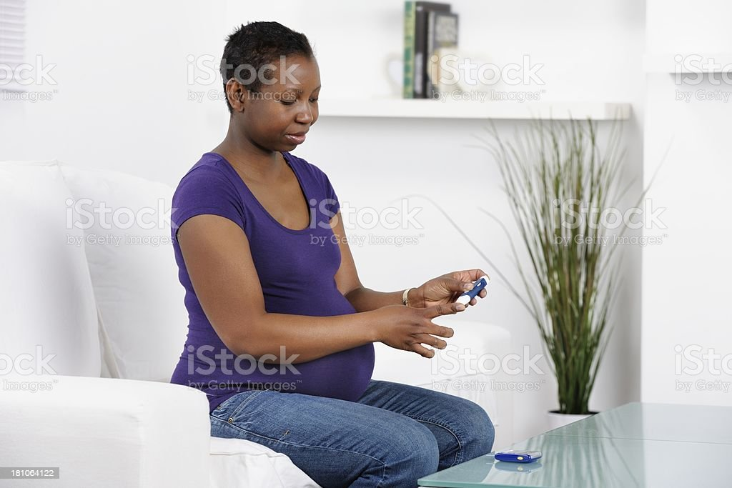 Pregnant African American Woman Monitoring Her Blood Glucose At Home royalty-free stock photo