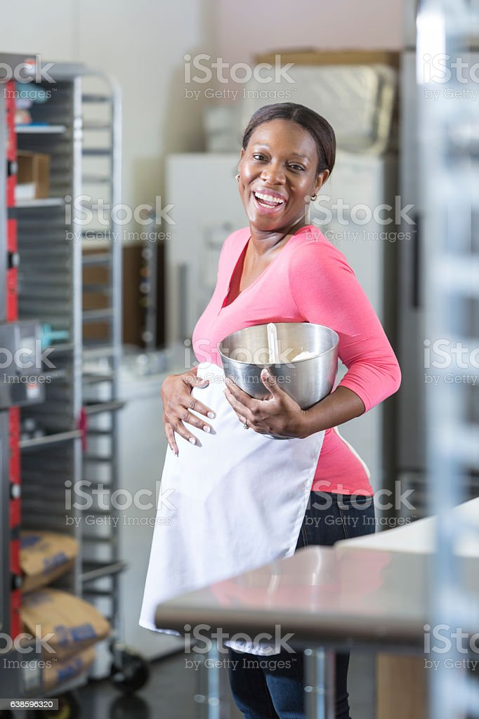 Pregnant, African American woman working in bakery stock photo