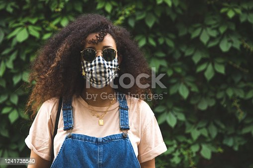 Portrait of a pregnant afro hair woman in the city wearing a cloth protective mask in Italy during Covid-19 coronavirus pandemic
