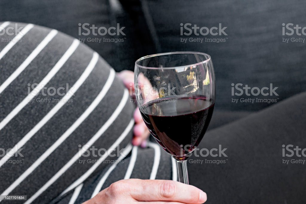 Pregnant and drinking alcohol stock photo