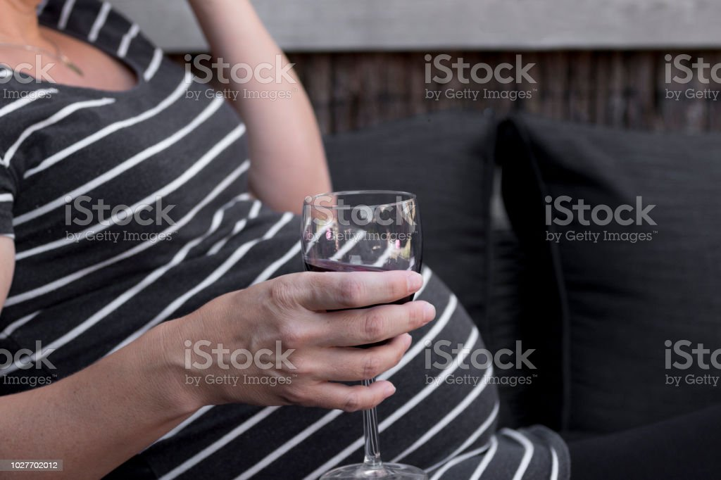 Pregnant and drinking stock photo