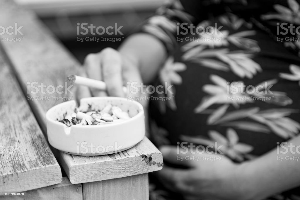 Pregnant and smoking cigarettes stock photo