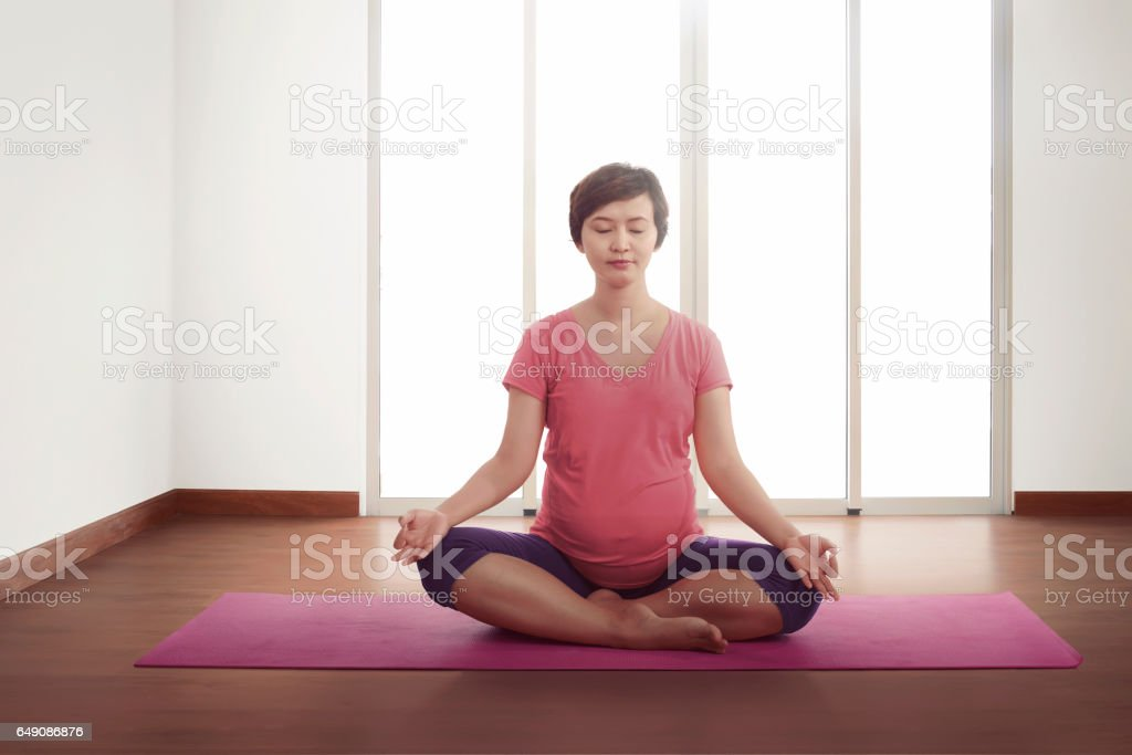 Pregnant asian woman exercising on pink mat stock photo