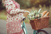 Pregnant belly against nature close-up. Pregnant girl retro French style with bicycle on a forest road. Beautiful pregnancy concept. Blonde happy woman with curly hair on nature background.