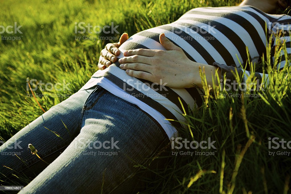 Pregnant Belly at Sunset A young woman, halfway through her pregnancy, lays in a field of green grass holding her hands on her stomach, the summer sun shining warmly on her.  Horizontal with copy space. Abdomen Stock Photo