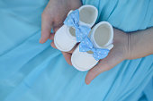 Pregnant belly with newborn baby booties