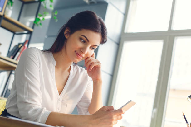 Pregnant business woman working at office motherhood sitting using smartphone stock photo