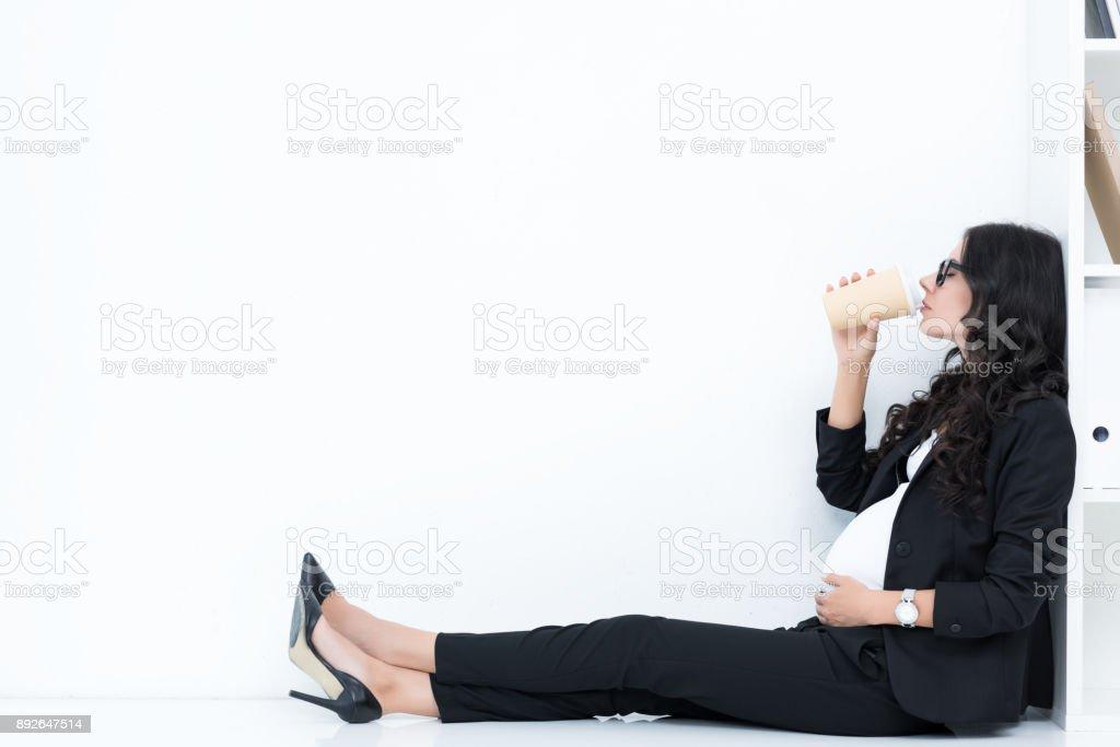 pregnant businesswoman drinking coffee stock photo