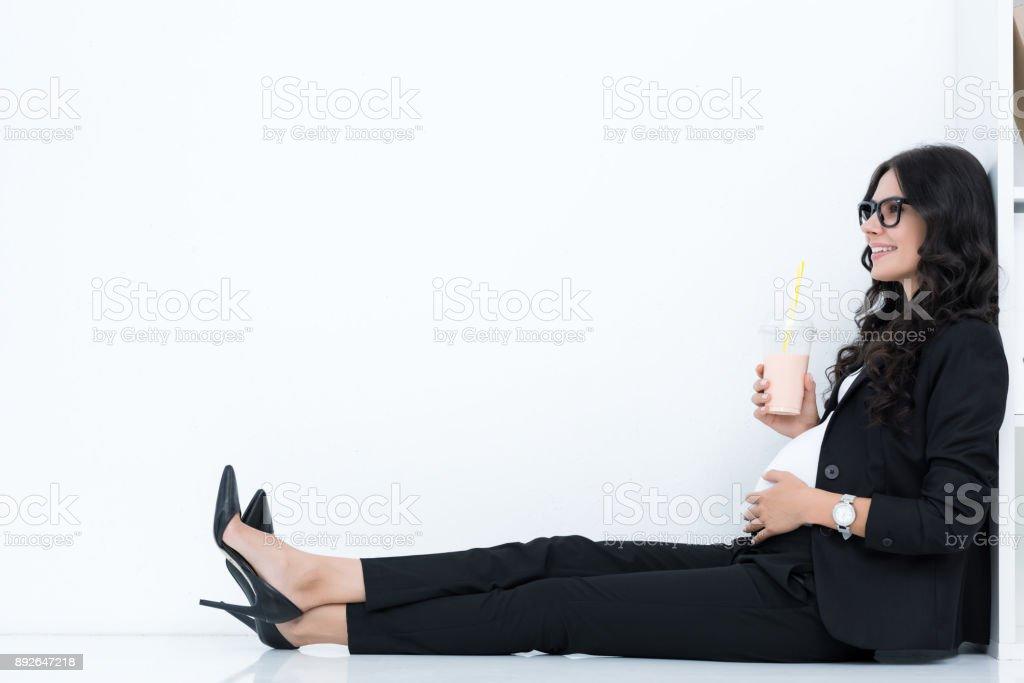pregnant businesswoman drinking milkshake stock photo