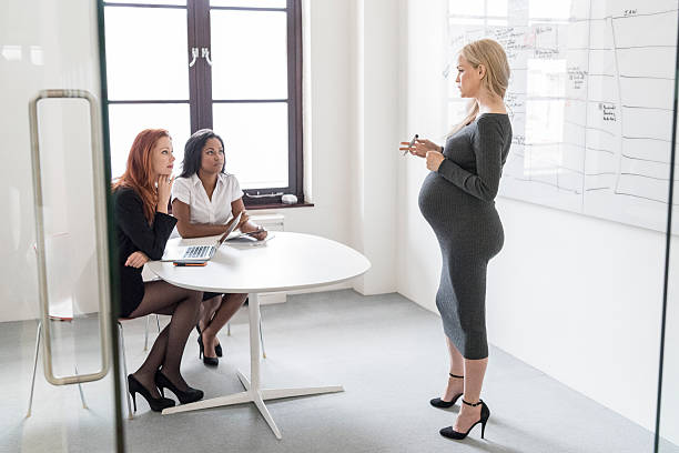 Pregnant businesswoman explaining to female colleagues in business meeting - foto de stock