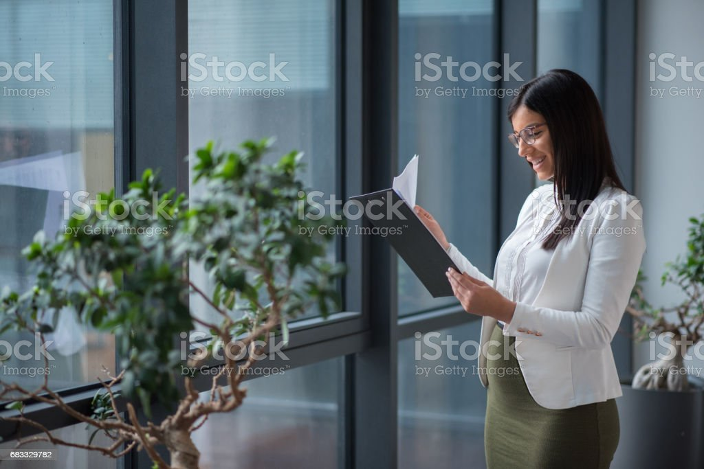 Zwangere zakenvrouw kijken naar documenten in office lobby royalty free stockfoto