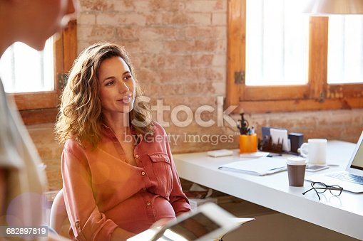 Pregnant businesswoman looking away at desk. Beautiful female professional is sitting in office. She is wearing shirt at workplace.