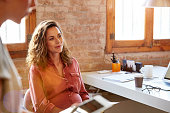 istock Pregnant businesswoman looking away at desk 682897819
