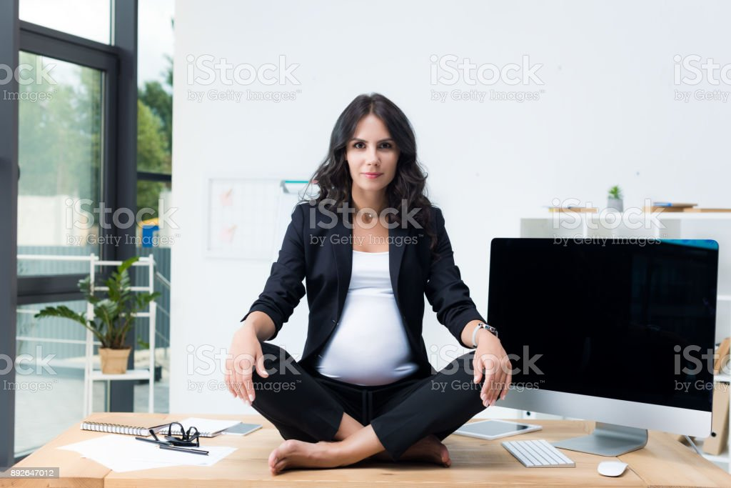pregnant businesswoman on table in lotus pose stock photo