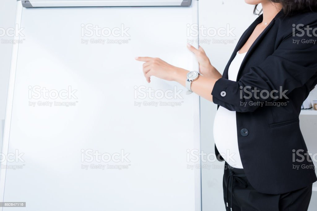 pregnant businesswoman pointing at blank whiteboard stock photo