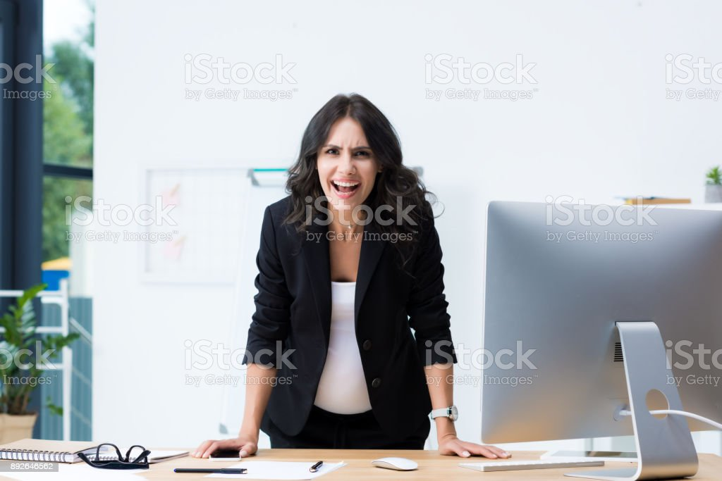 pregnant businesswoman screaming at camera stock photo