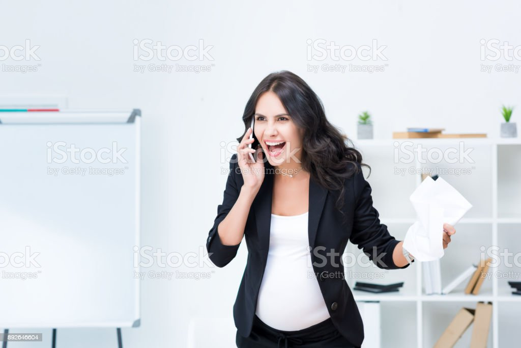 pregnant businesswoman shouting at phone stock photo