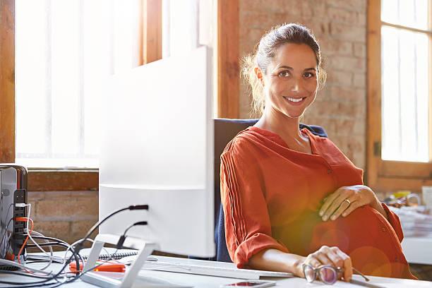 Pregnant businesswoman sitting at computer desk stock photo