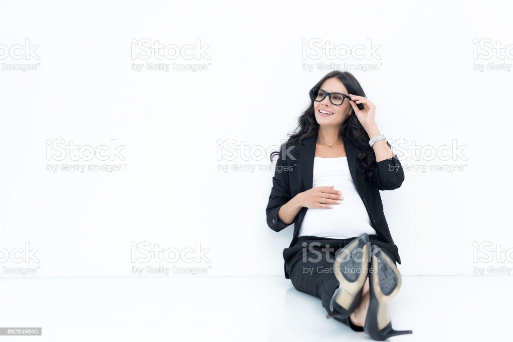 pregnant businesswoman sitting on floor stock photo