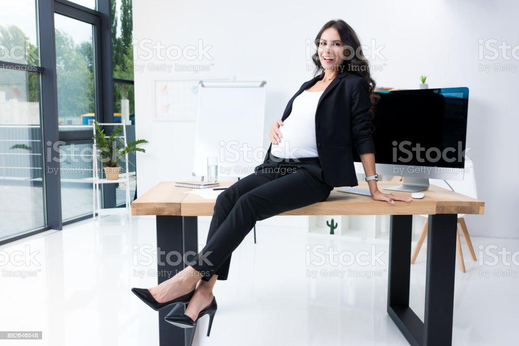 pregnant businesswoman sitting on worktable stock photo