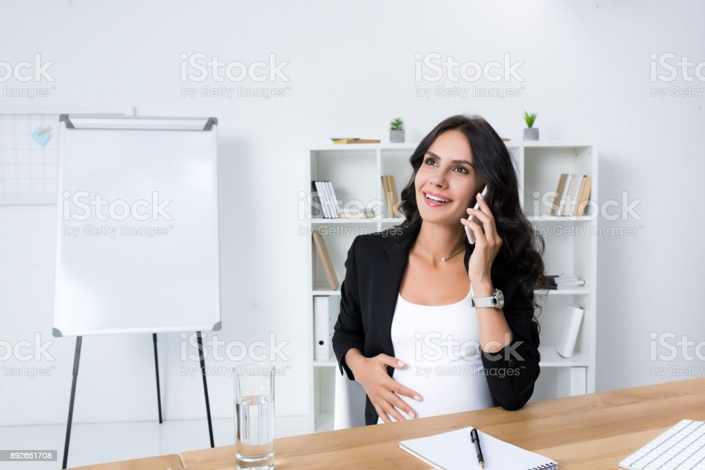 pregnant businesswoman talking by phone stock photo