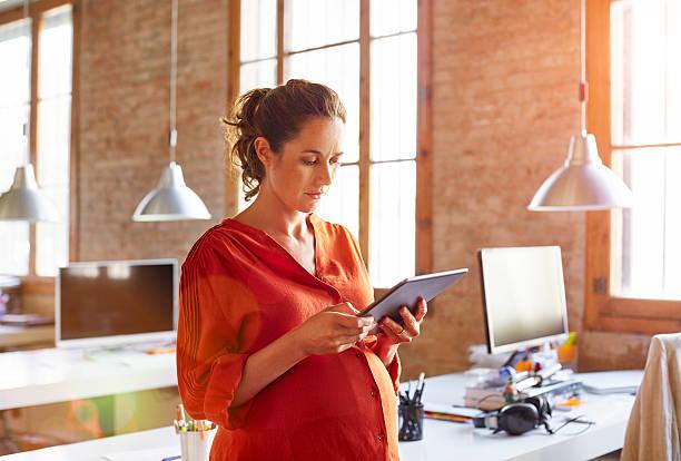 pregnant businesswoman using tablet pc in office - schwanger werden rechner stock-fotos und bilder