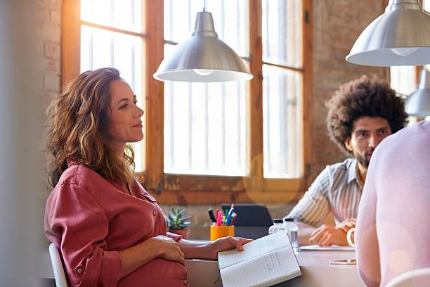 pregnant businesswoman with colleagues in office - schwanger werden rechner stock-fotos und bilder