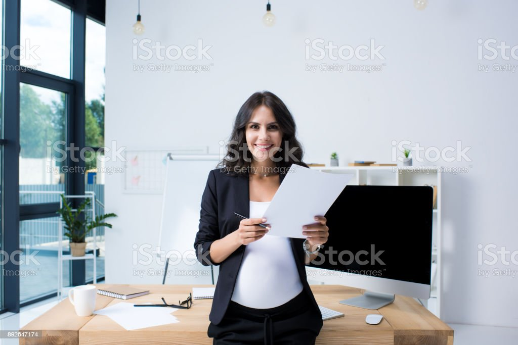 pregnant businesswoman with paperwork stock photo