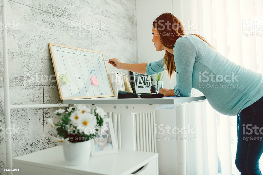 Pregnant Businesswoman Working In Her Home Office. stock photo