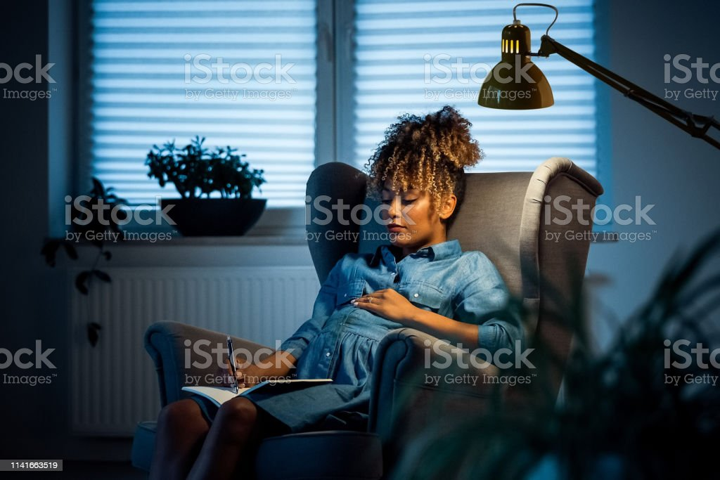 Pregnant businesswoman writing on book in office Pregnant businesswoman writing on book. Female expertise is relaxing on armchair in new office. She is wearing business casuals. 35-39 Years Stock Photo