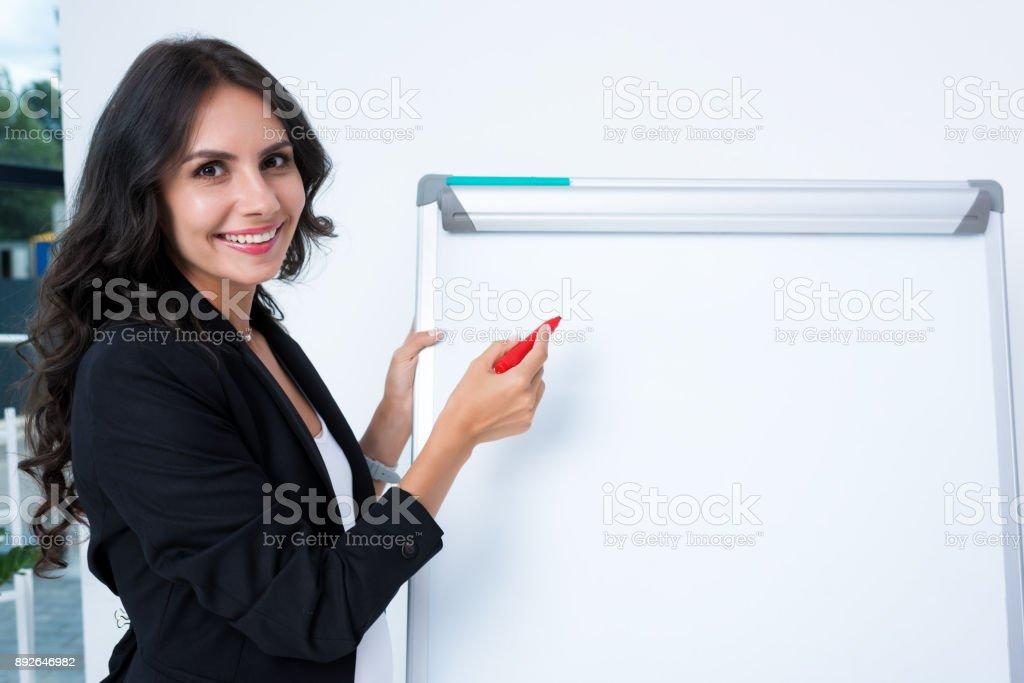 pregnant businesswoman writing on whiteboard stock photo