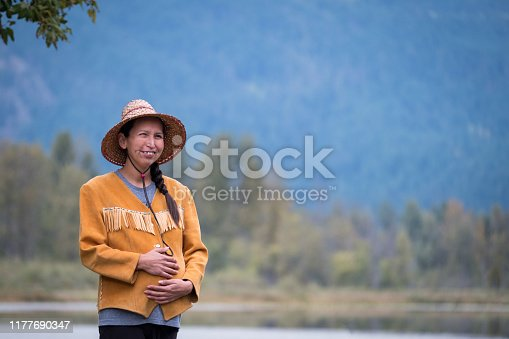 A First Nations woman enjoys a morning walk by the lake. She is pregnant and admiring the beauty in nature. She is holding her stomach