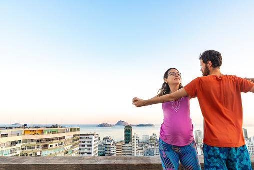 Pregnant couple dancing stretching Ipanema rooftop