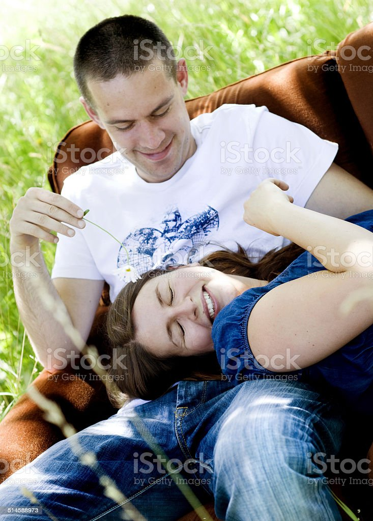 Pregnant couple in nature on sofa royalty-free stock photo
