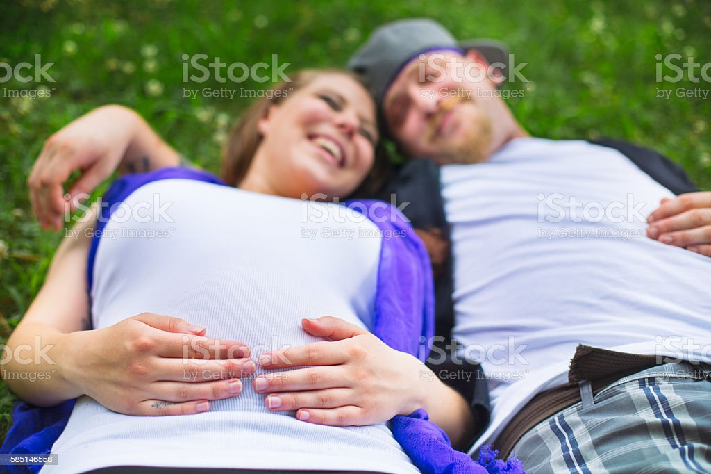 pregnant couple laying in grass laughing with focus on hands - foto de stock