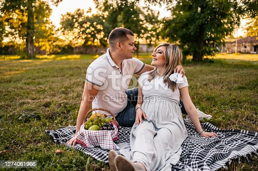 Young happy cute pregnant couple on picnic in public park.