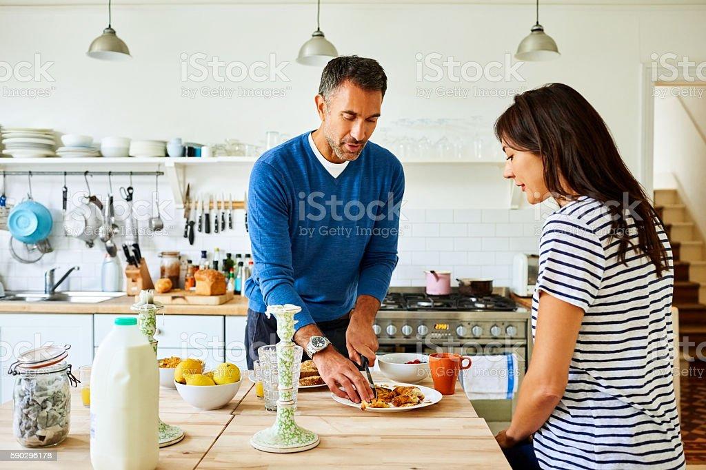 Pregnant couple preparing breakfast in kitchen royaltyfri bildbanksbilder