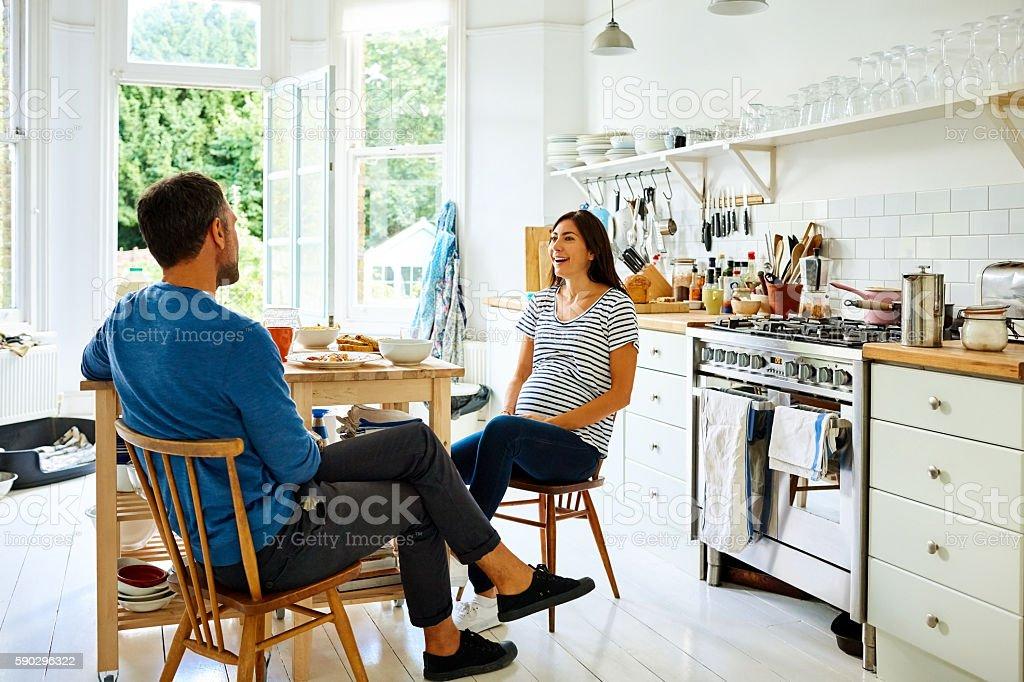 Pregnant couple sitting at breakfast table royaltyfri bildbanksbilder