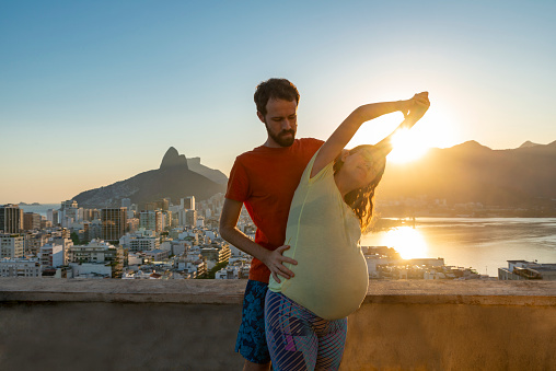 Pregnant couple stretching on rooftop sunset