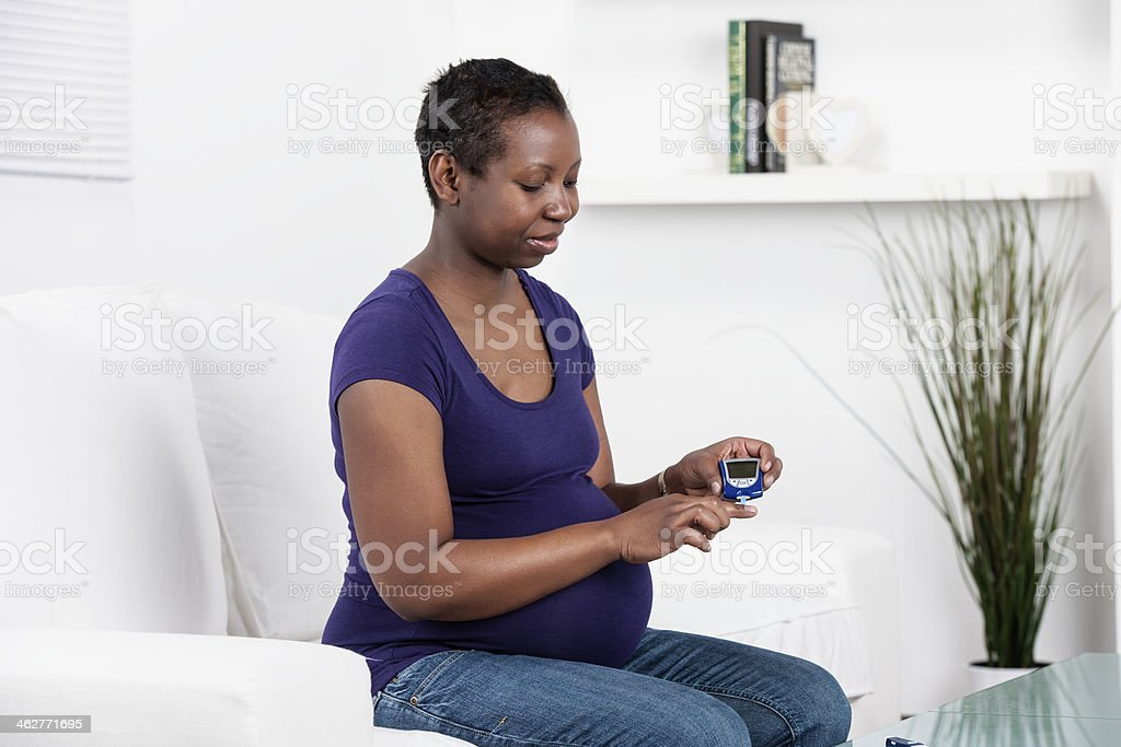 Pregnant Diabetic Checking Her Blood Sugar/ Glucose At Home stock photo